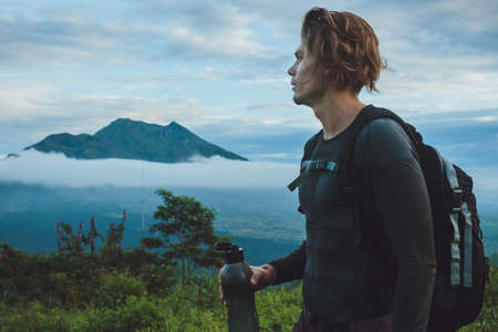 water drink: Outdoor portrait of Young man looking on Batur volcano and Agung mountain view at morning from Kintamani, Bali, Indonesia and drink water