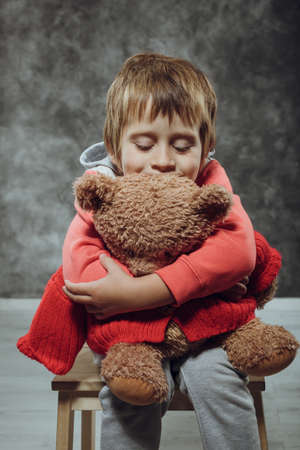5 years old: Boy 5 years old hugging big teddy bear sits on a chair Stock Photo