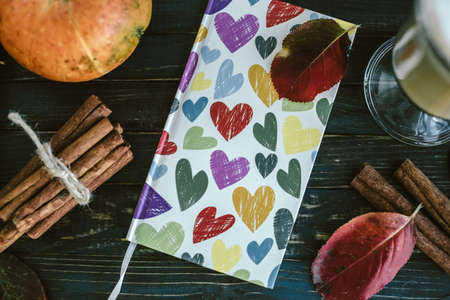 Notebook with hearts, pumpkin, cinnamon and leaves. Autumn concept Stock Photo