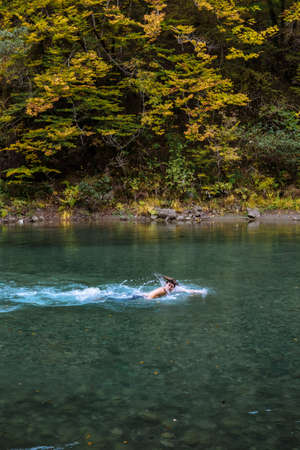 Young sports man bathing in a mountain lake in the fall