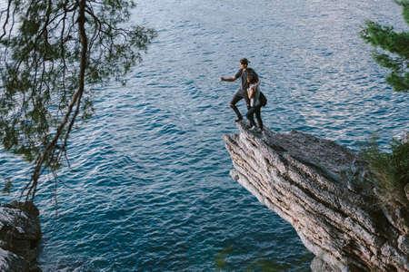 kinfolk: Happy Man and women sit down on a rock mountain in Montenegro, freedom cocept