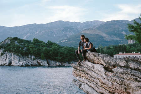 sit down: Happy Man and women sit down on a rock mountain in Montenegro, freedom cocept