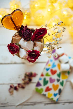 lolipop: Glass with coffee  with dried rose flower, heart lolipop, marshmallow, book on light background