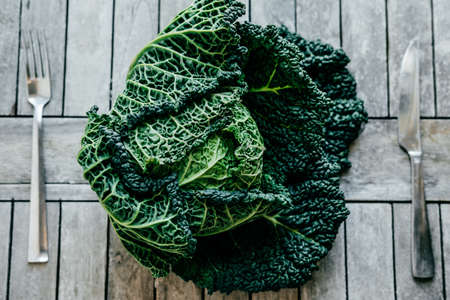 Fresh Green Kale most useful vegetables on wooden background with a fork and knife