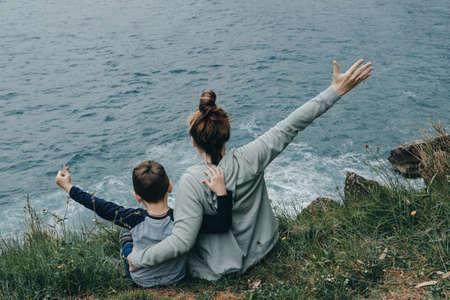 Achteraanzicht van vrouw en haar zoon steeg hun handen omhoog op de berg boven de zee. Freedom concept Stockfoto