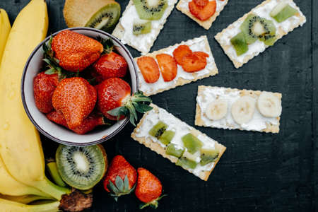 tabla de quesos: Delicious Crackers with cheese and fruits: bananas, strawberries and kiwi on a black background, Top view