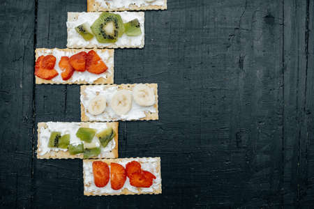 cheeseboard: Snacks on a handmade Crackers with cheese and fruits: bananas, strawberries and kiwi on a black background