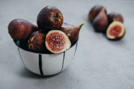 Fresh figs in bawl on gray background Stock Photo