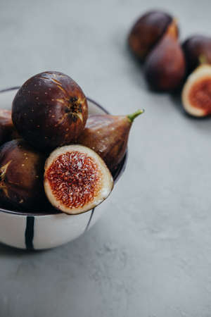 Vertical photo of Fresh figs in bawl on gray background