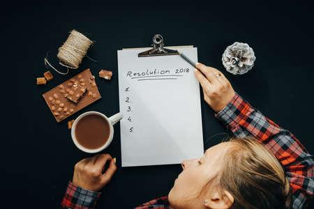 Blanco album papier met Nieuwjaar resolutie inscriptie en slapende vrouw met potlood, chocolade, cacao, kegel op zwarte achtergrond, bovenaanzicht, plat leggen Stockfoto