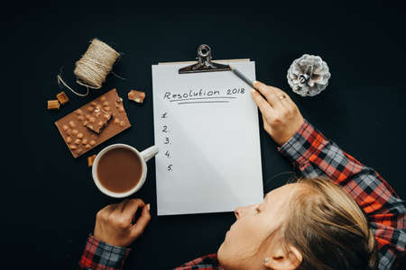 Blank album paper with New Year Resolution inscription and sleeping woman with pencil, chocolate, cocoa, cone on black background, top view, flat lay Zdjęcie Seryjne - 87211605