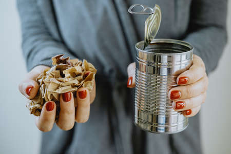 Female hands with an iron jar and paper. Separate collection of garbage