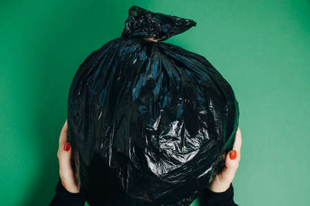 Waste management concept. Woman Hands With garbage on the green Background. Top View
