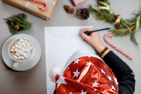Cocoa with marshmallow and Boy writing letter to Santa Claus at Christmas. Top view. Stock Photo