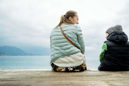 Back view of a boy and mom sitting on a wooden board and looking at the sea Stock Photo