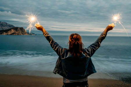 Back view of young happy smiling woman holding sparkler near the sea