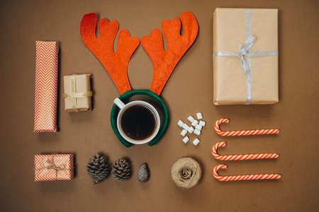 Christmas background with santa hat, Coffee with marshmallows and gifts on brown table. Top view, flat lay