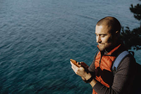 Man traveler in a red waistcoat watching world map on mobile phone while relaxing near sea