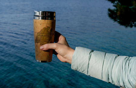 Closeup photo of thermal mug with tea in travelers hand over sea view