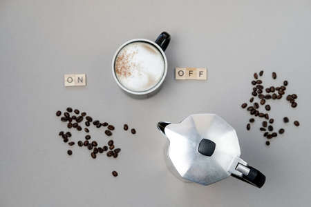 Cup of coffee switching on, grains and coffee pot on grey background. Top view, flat lay Stock Photo
