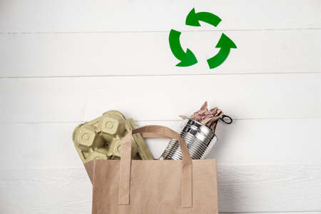Separate garbage collection: paper bag, egg packing and aluminum can. Eco concept. Flat lay