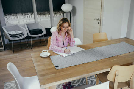 Beautiful young woman freelancer works in an apartment with phone and notebook. Business concept