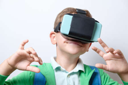 Cute schoolboy with blue backpack wearing virtual reality helmet with arms stretched forward on a white background