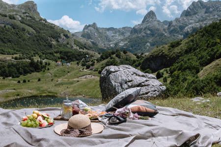 Romantic picnic in the mountains Montenegro. Young woman and man eating Fruit, lemonade and pastries