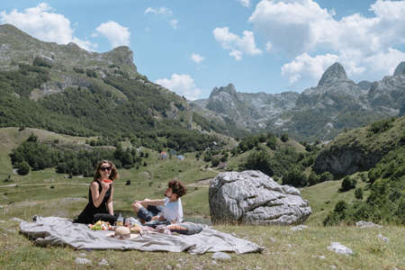 Romantic picnic in the mountains Montenegro. Young woman and man drinking lemonade  and eating Fruit.