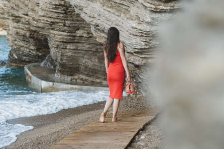 Back view of a young beautiful woman in red dress walking at the beach Banco de Imagens
