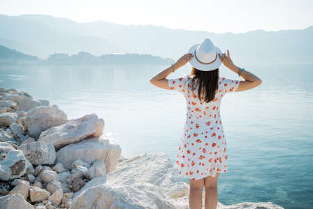 Back view of a young beautiful woman holding her white hat at the beach and looking to the horizon. Banco de Imagens