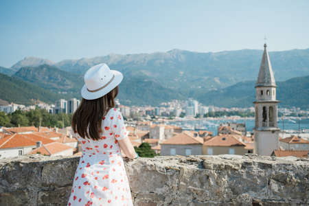 Back view of a young beautiful woman with hat  looking to the old town Budva, Montenegro