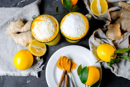Turmeric latte or golden milk in glasses with ginger and lemons on a black  table