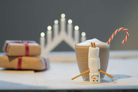 Marshmallow snowman and cocoa on the background of Christmas lights