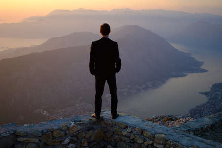 back of a young man in costume standing on a mountain at sunset. The groom or businessman looks from the top. Banque d'images