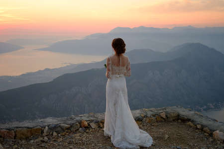 back of the bride in white dress standing on top of the mountain at sunset Banco de Imagens