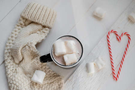 Top view of Cocoa with marshmallows and chocolate on a background of Christmas lights