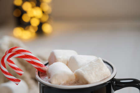Close up Cocoa with marshmallows and chocolate on a background of Christmas lights