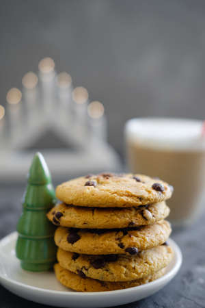 Christmas cookies with chocolate on the background of candles.