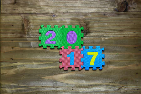 block number: Letter puzzle block and number 2017 with wood background