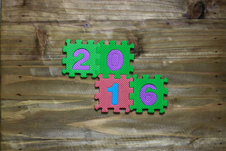 block number: Letter puzzle block and number 2016 with wood background