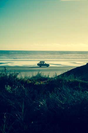 4x4 RV van on deserted beach  Driving towards the sun, leaving a nice shadow  Freedom feeling, cruising the beach with a packed car  photo
