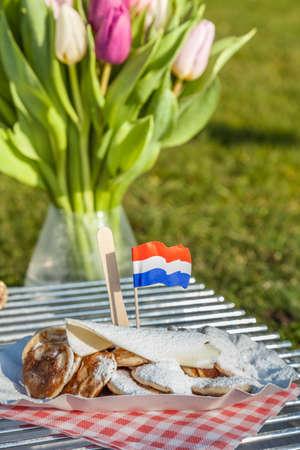 Kleine Nederlandse pannenkoeken geserveerd met boter, suger en een Nederlandse vlag.