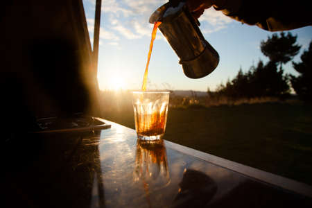 percolator: While travelling you still love your coffee so you travel with a percolator and have awesome coffee on the road  Nice sunlight hitting the glass while pouring Stock Photo