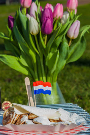suger: Small Dutch pancakes served with butter, suger and a Dutch flag.