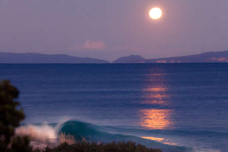 Full moon above the ocean with a crashing wave and the moon lighting up the water
