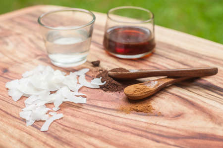 Coconut oil, coconut rashes, ground vanilla beans and maple sirup on a wooden background