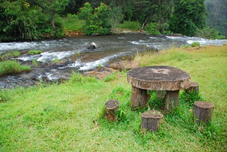 Picnic wood table next to river Stock Photo