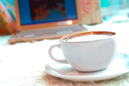 Coffee cup in front of laptop background photo