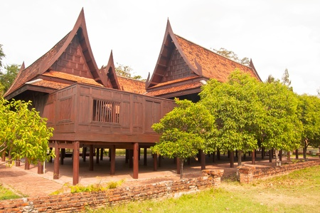 Thai House building from wood Surrounded by red brick walls